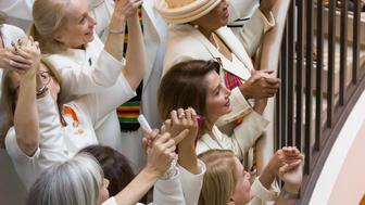 House Speaker Nancy Pelosi of Calif., center right, is joined by other women wearing white, as they hold hands while posing for a group photo before the State of the Union address by President Donald Trump, on Capitol Hill, Tuesday, Feb. 5, 2019 in Washington. (AP Photo/Alex Brandon)