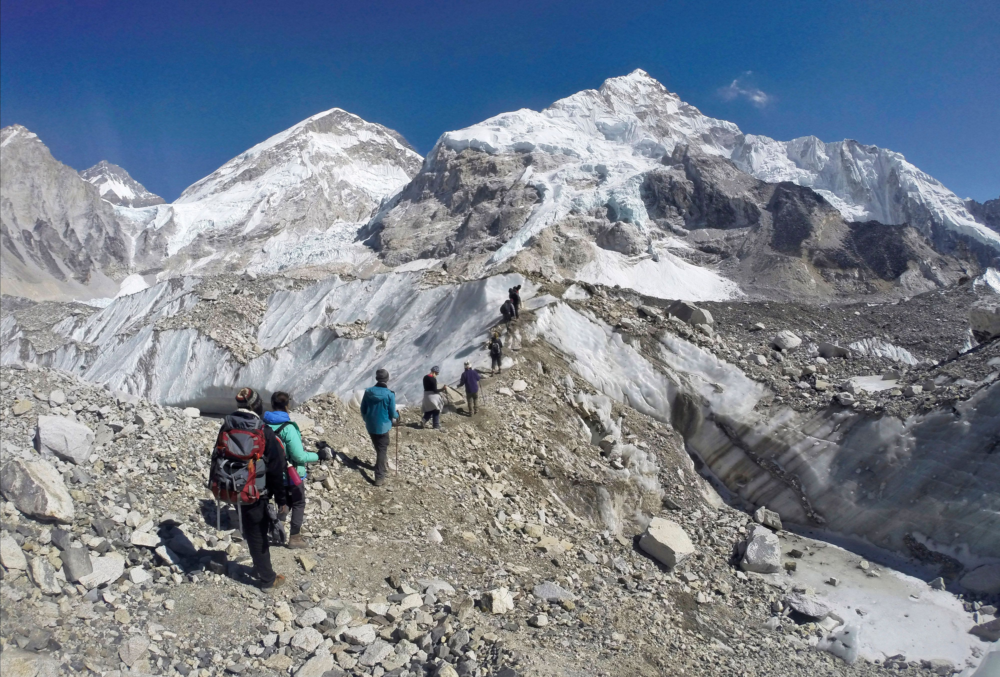 FILE - In this Monday, Feb. 22, 2016 file photo, trekkers pass through a glacier at the Mount Everest base camp, Nepal. One-third of Himalayan glaciers will melt by the end of the century due to climate change, threatening water sources for 1.9 billion people, even if current efforts to reduce climate change succeed, according to an assessment released Monday, Feb. 4, 2019. by the International Centre for Integrated Mountain Development. (AP Photo/Tashi Sherpa, file)