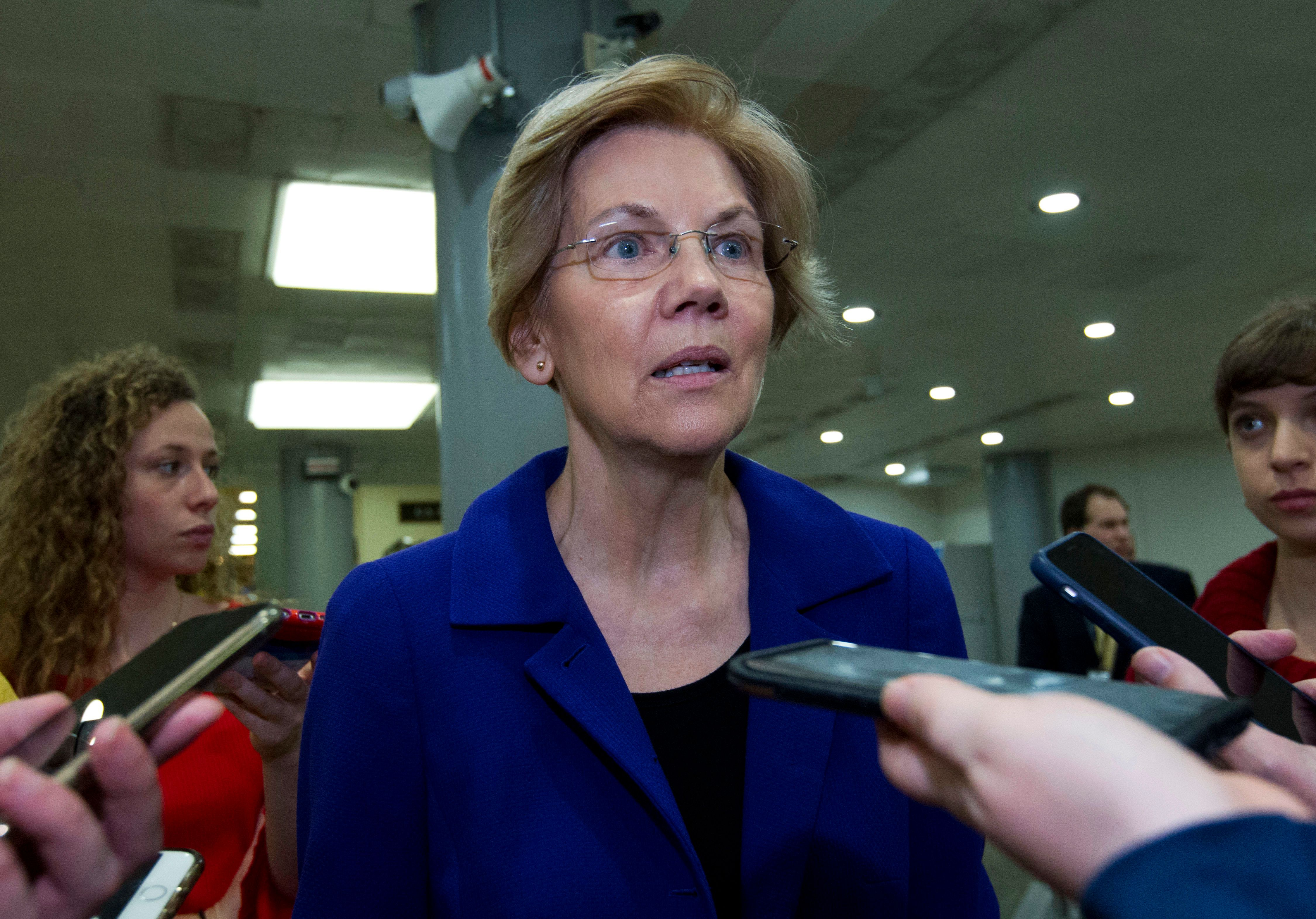 Sen. Elizabeth Warren D-Mass., speaks to reporters on his way to her office, as the Senate takes up a House-passed bill that would pay for President Donald Trump's border wall and avert a partial government shutdown, at the Capitol in Washington, Friday, Dec. 21, 2018. (AP Photo/Jose Luis Magana)