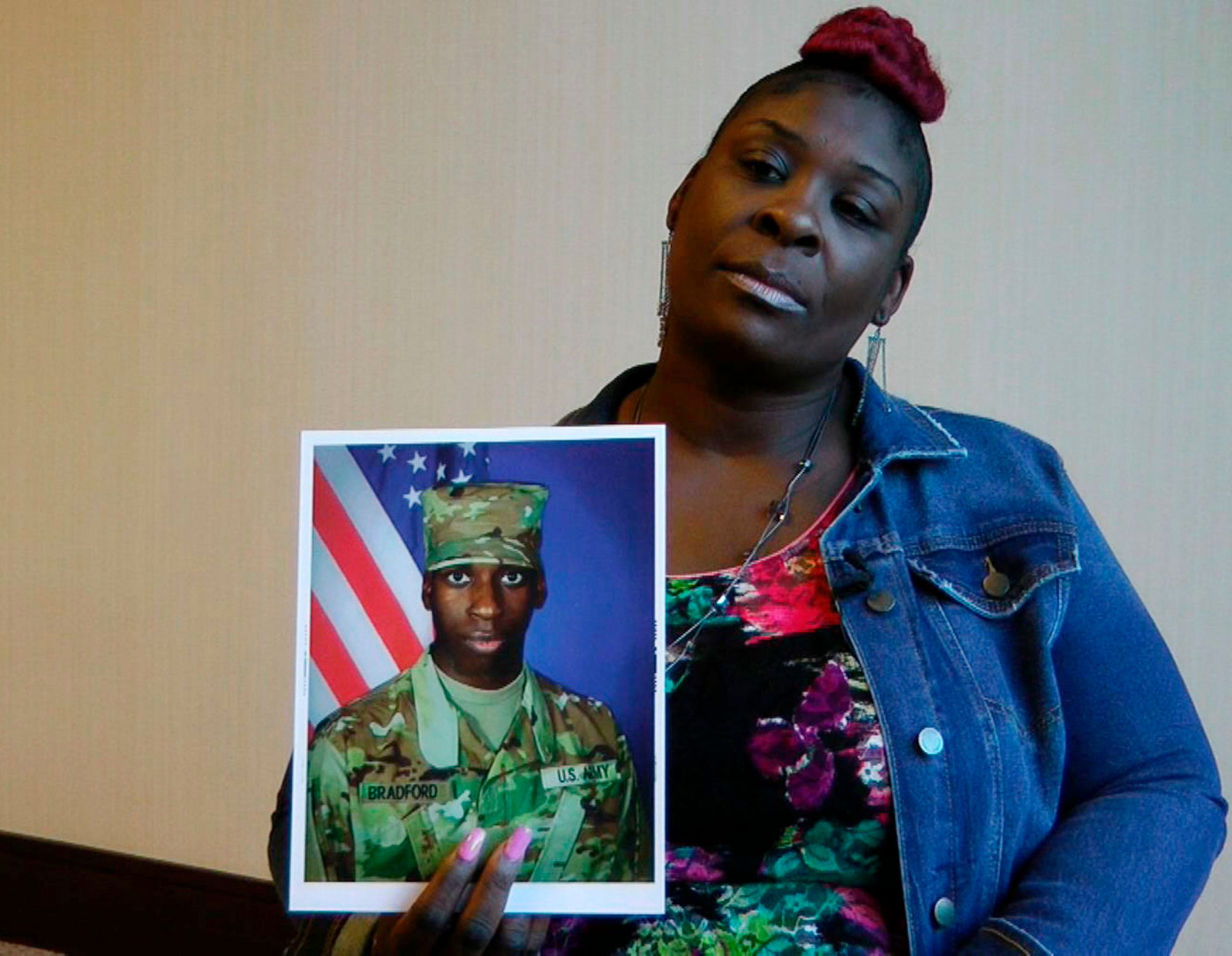 """April Pipkins holds a photograph of her deceased son, Emantic """"EJ"""" Bradford Jr., who was fatally shot by police after being m"""