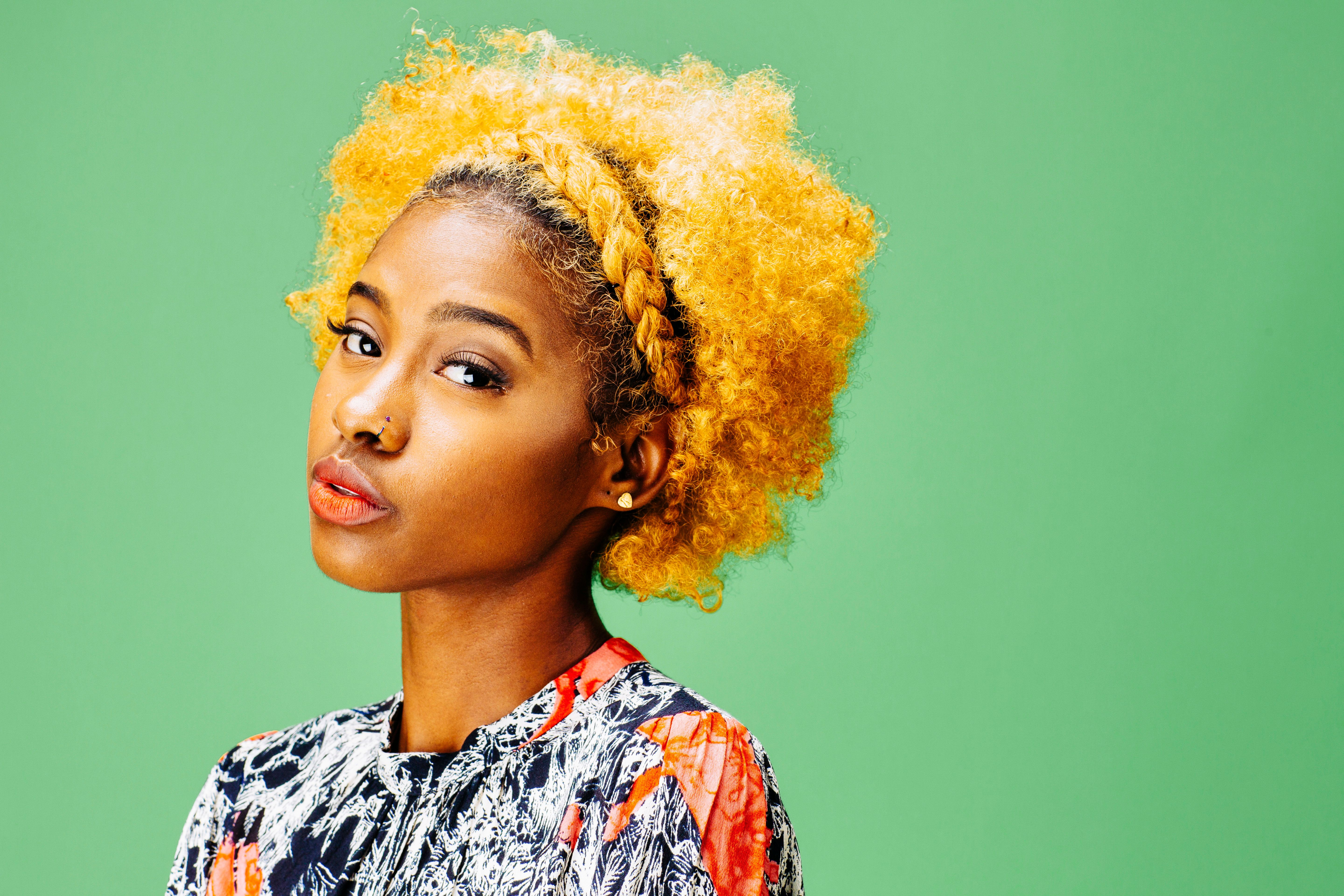 Horizontal portrait of a lovely young girl with bleached curly hair, in front of a green background