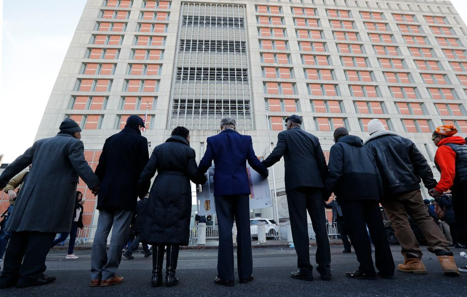 Community and religious leaders join hands to protest and pray outside the Metropolitan Detention Center,...