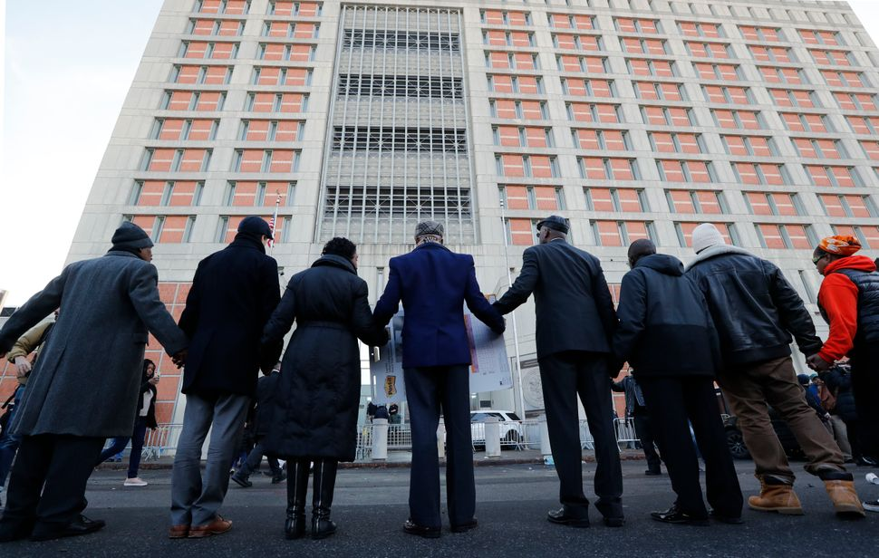 Community and religious leaders join hands to protest and pray outside the Metropolitan Detention Center, a federal prison wh