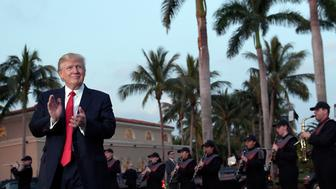 FILE- In this Feb. 5, 2017, file photo, President Donald Trump listens to the Palm Beach Central High School Band as they play at his arrival at Trump International Golf Club in West Palm Beach, Fla. (AP Photo/Susan Walsh, File)