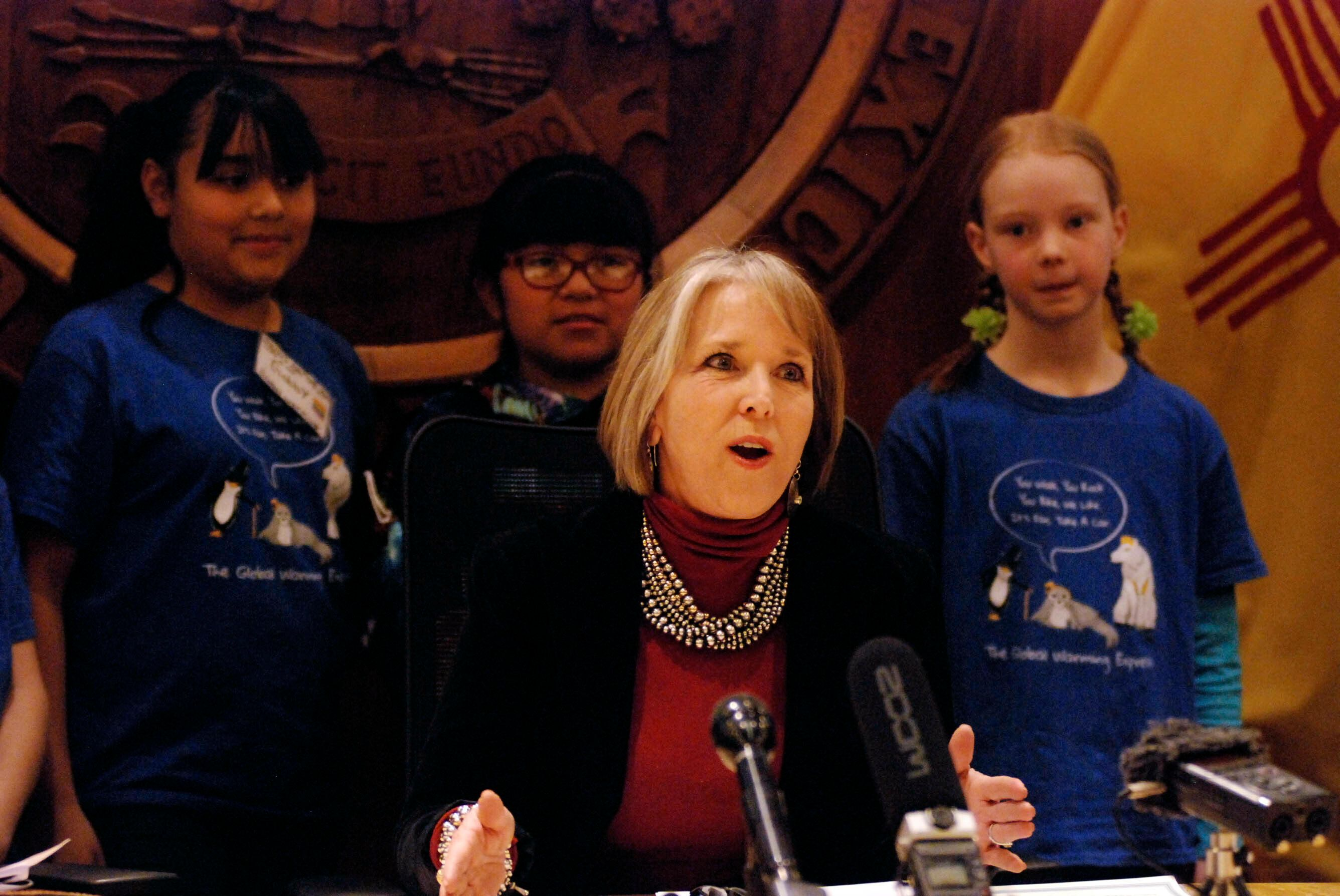 New Mexico Gov. Michelle Lujan Grisham, center, signs an executive order for state agencies to aggressive pursue strategies to reduce greenhouse gas emissions on Tuesday, Jan. 29, 2019, in Santa Fe, N.M. flanked by student activists on global warming issues. The order endorses goals of the 2015 Paris climate agreement to limit global warming and sets in motion new efforts to encourage renewable energy development, improve energy efficiency for buildings, safeguard air quality and possibly set new vehicle emission standards. (AP Photo/Morgan Lee)