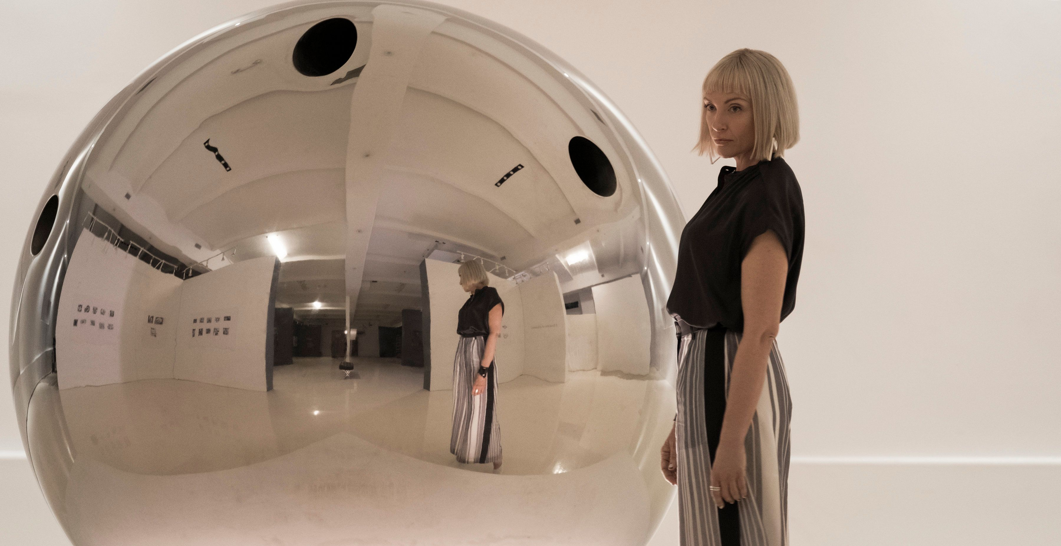 "Gretchen (Toni Collette) alongside hit artwork ""The Sphere"" in ""Velvet Buzzsaw."""