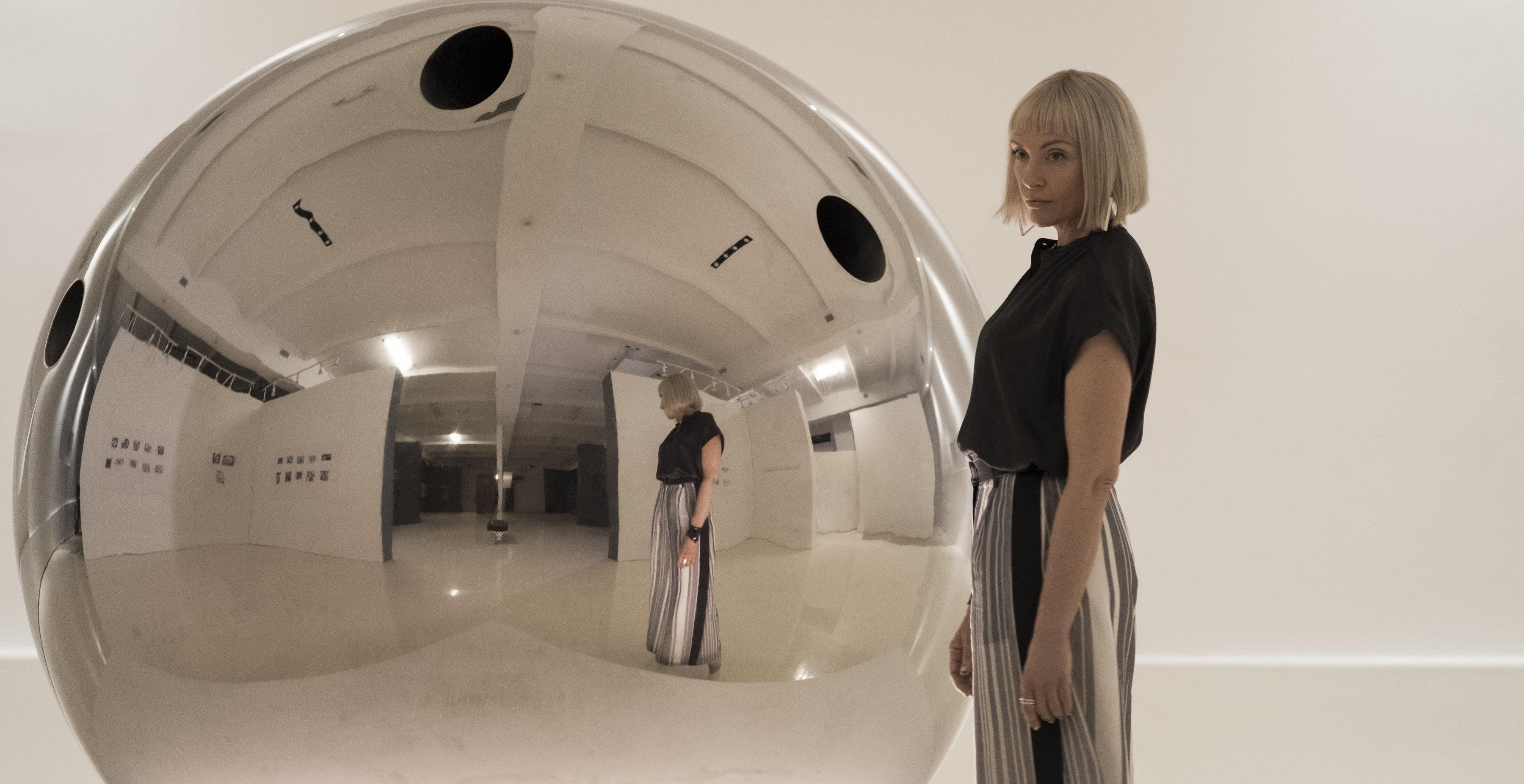 "Gretchen (Toni Collette) alongside a hit artwork, ""The Sphere,"" in ""Velvet Buzzsaw."""