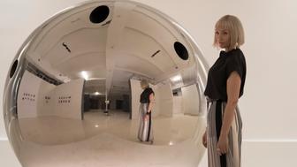 """Gretchen (Toni Collette) alongside hit artwork """"The Sphere"""" in """"Velvet Buzzsaw."""""""