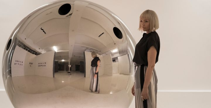 "Gretchen (Toni Collette) alongside a hit artwork, ""The Sphere,"" in ""Velvet Buzzsaw."""
