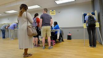 RALEIGH, NC - MARCH 15:  A lone North Carolina State University student, right, votes in the primaries at the provisional ballot booth at Pullen Community Center on March 15, 2016 in Raleigh, North Carolina. The North Carolina primaries is the state's first use of the voter ID law, which excludes student ID cards. Wake County was among the highest use of provisional ballots, where those voters had home addresses on or near campuses. The Board of Elections will review voter's reasonable impediment form submitted with their provisional ballots to determine if their vote counts. The state's voter ID law is still being argued in federal court. (Photo by Sara D. Davis/Getty Images)