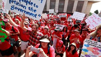 Teachers rally outside the Capitol on Monday, April 30, 2018, in Phoenix on their third day of walk outs. Teachers in Arizona and Colorado walked out of their classes over low salaries keeping hundreds of thousands of students out of school. It's the latest in a series of strikes across the nation over low teacher pay. (AP Photo/Matt York)