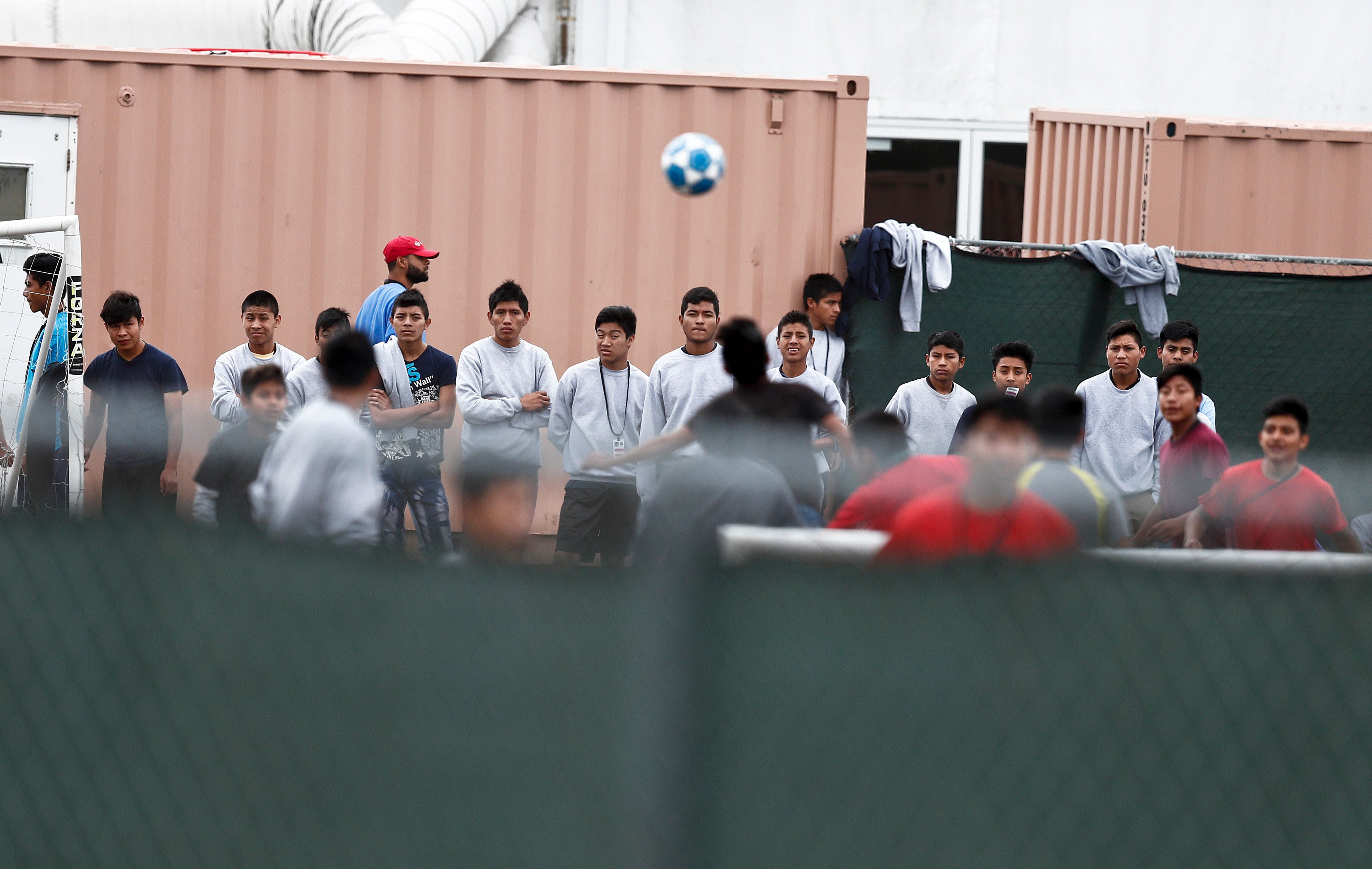 An immigrant boy plays soccer as others gather and watch at the Homestead Temporary Shelter for Unaccompanied Children a former Job Corps site that now houses them Monday, Dec. 10, 2018, in Homestead, Fla. (AP Photo/Brynn Anderson)