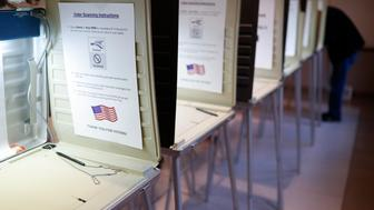 FILE- In this Nov. 8, 2016, file photo a lone voter fills out a ballot alongside a row of empty booths at a polling station in the Terrace Park Community Building on Election Day in Cincinnati. An expert panel of the National Academy of Sciences called for fundamental reforms to ensure the integrity of the U.S. election system. The report calls for replacing rickety voting machines with more-secure voting systems that use paper ballots or equivalents, and other measures such as a particular form of postelection audit aimed at spotting fraud. (AP Photo/John Minchillo, File)