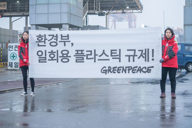 그린피스 활동가들이 평택항에서 환경부가 기업이 제품 포장재, 용기 등에 제한 없이 소비하고 있는 일회용 플라스틱량을 규제할 것을 요구하는 현수막을 들고