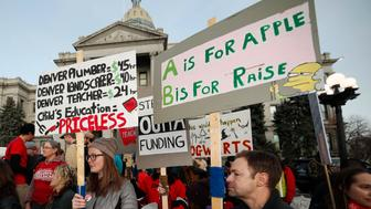 FILE - In this Wednesday, Jan. 30, 2019, file photo, teachers from the Denver Public Schools carry placards as they wait to march after a rally in support of a strike outside the State Capitol in Denver. Denver teachers are planning to strike Monday, Feb. 11, 2019 after failed negotiations with the school district over base pay. (AP Photo/David Zalubowski, File)