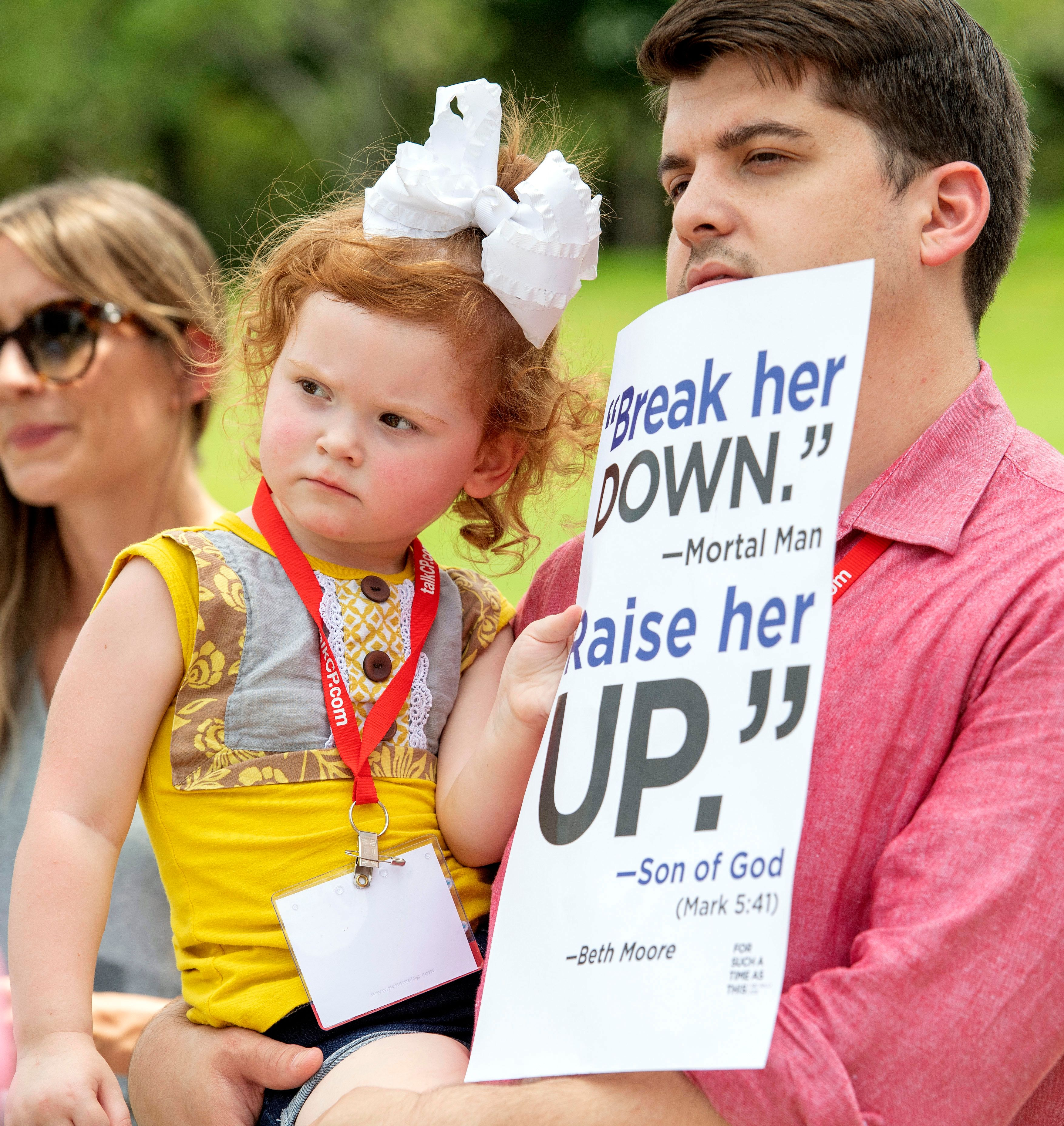 Chase Crawford, a Southern Baptist Convention messenger from Arkansas, and his 2-year-old daughter Chloe Jean Crawford listen to speakers during a rally protesting the Southern Baptist Convention's treatment of women on Tuesday, June 12, 2018 outside the convention's annual meeting at the Kay Bailey Hutchison Convention Center in Dallas. (AP Photo/Jeffrey McWhorter)