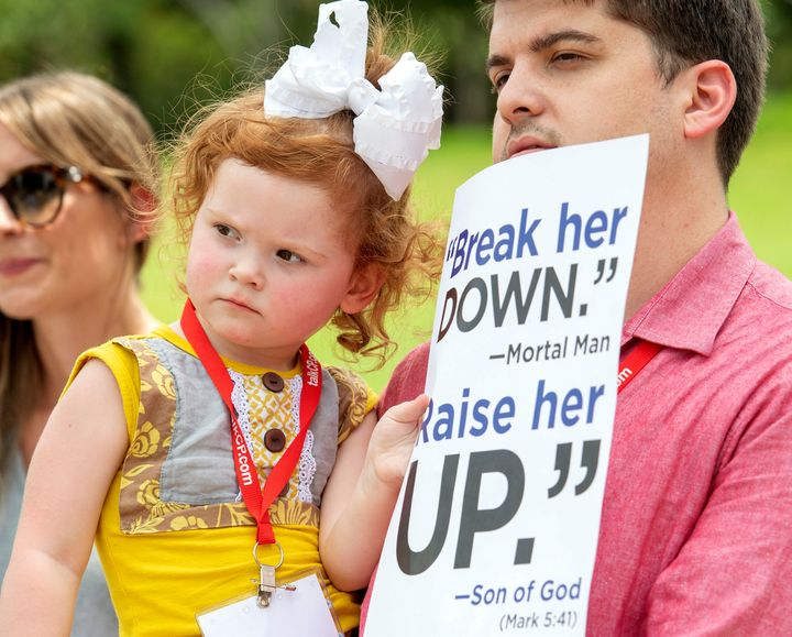 A Southern Baptist Convention member and his 2-year-old daughter attend a rally on June 12, 2018, protesting the Southern Bap