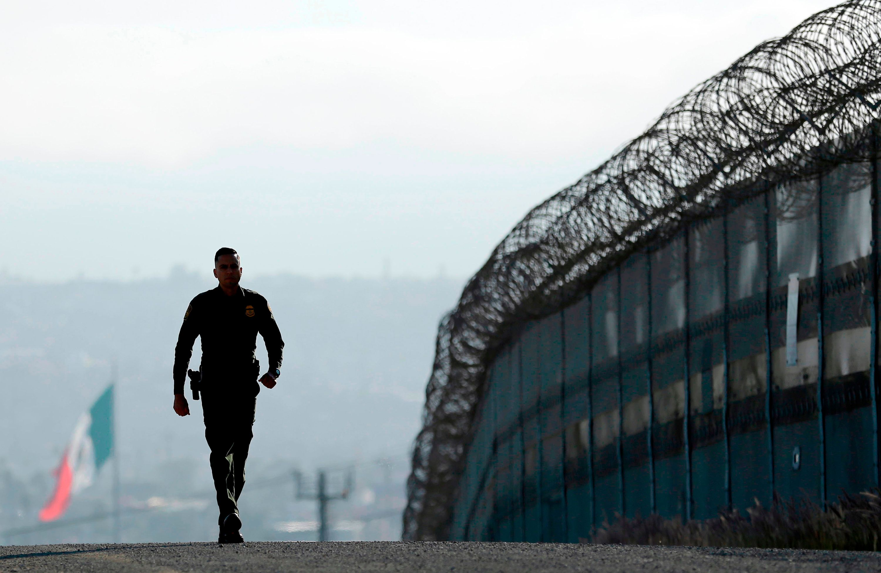 FILE - In this June 22, 2016 file photo, Border Patrol agent Eduardo Olmos walks near the secondary fence separating Tijuana, Mexico, background, and San Diego in San Diego. California National Guard troops have started training with the U.S. Customs and Border Patrol to be camera operators, radio dispatchers, intelligence analysts and fill other support roles to free up more agents to patrol the Mexican border. (AP Photo/Gregory Bull, File)