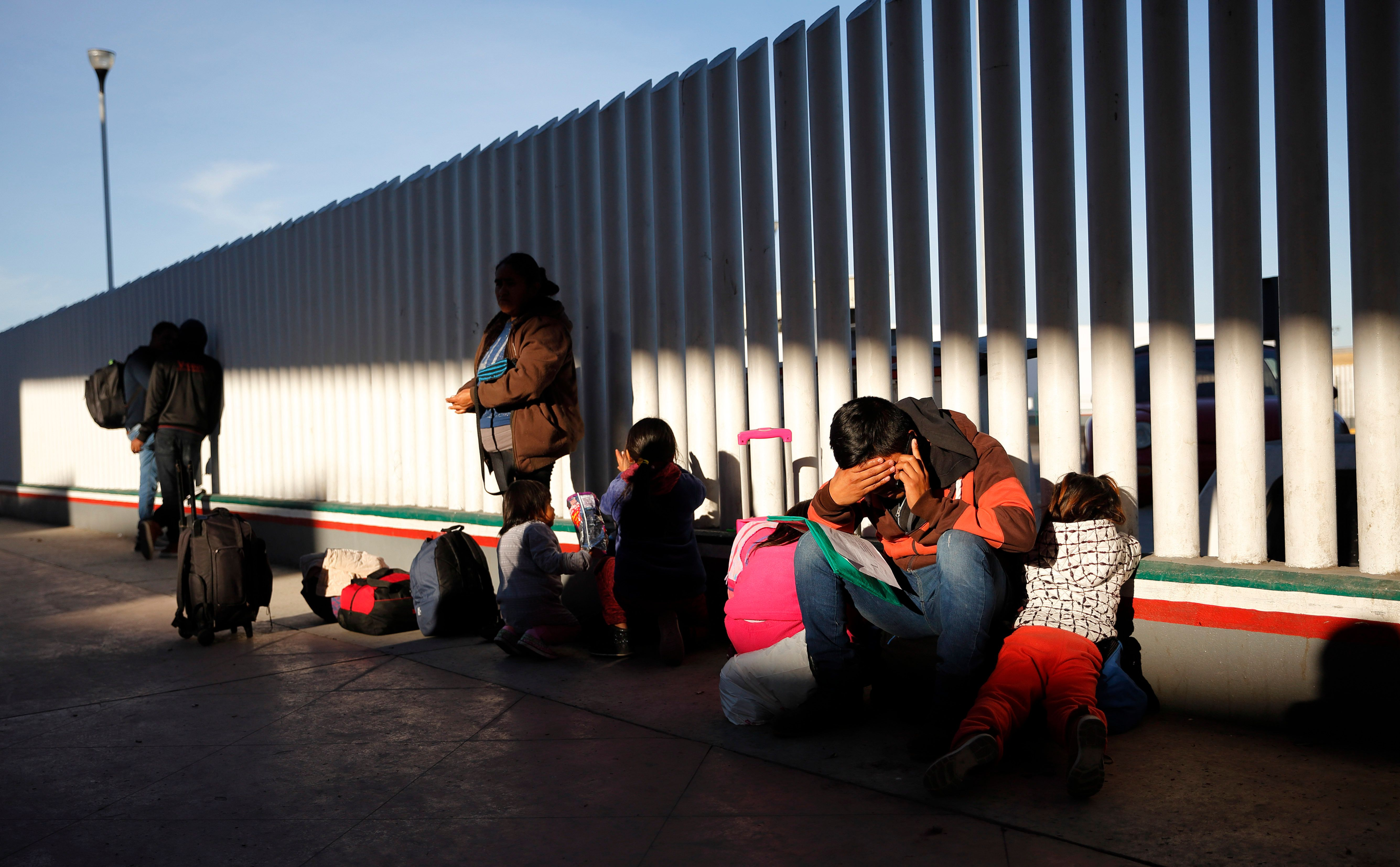 A migrant sits with his children as they wait to hear if their number is called to apply for asylum in...