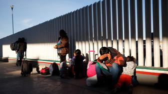 A migrant sits with his children as they wait to hear if their number is called to apply for asylum in the United States, at the border, Friday, Jan. 25, 2019, in Tijuana, Mexico. The Trump administration on Friday will start forcing some asylum seekers to wait in Mexico while their cases wind through U.S. courts, an official said, launching what could become one of the more significant changes to the immigration system in years. (AP Photo/Gregory Bull)