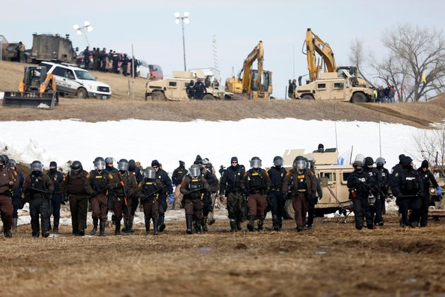 Law enforcement officers advance into the main opposition camp against the Dakota Access Pipeline near...