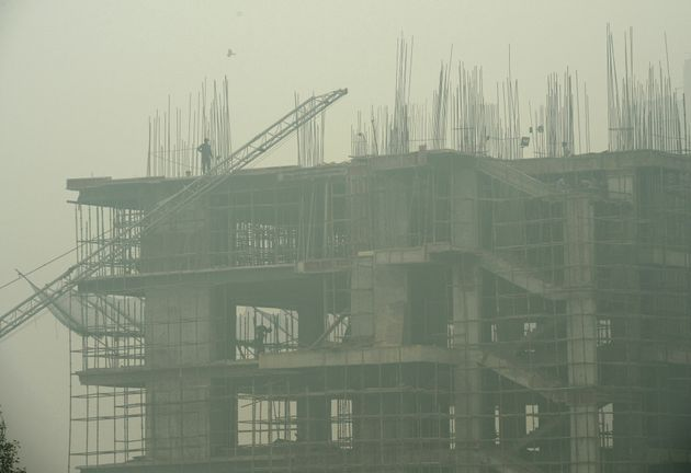 File photo of labourers working in an under-construction building as smog covers the capital's skyline...