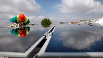 SolarCity Photovoltaics installer Victor Zapata uses a ban saw to make cuts while assembling thin film technology solar panels at the home of Andrew Kin in Los Angeles.  (Photo by Allen J. Schaben/Los Angeles Times via Getty Images)