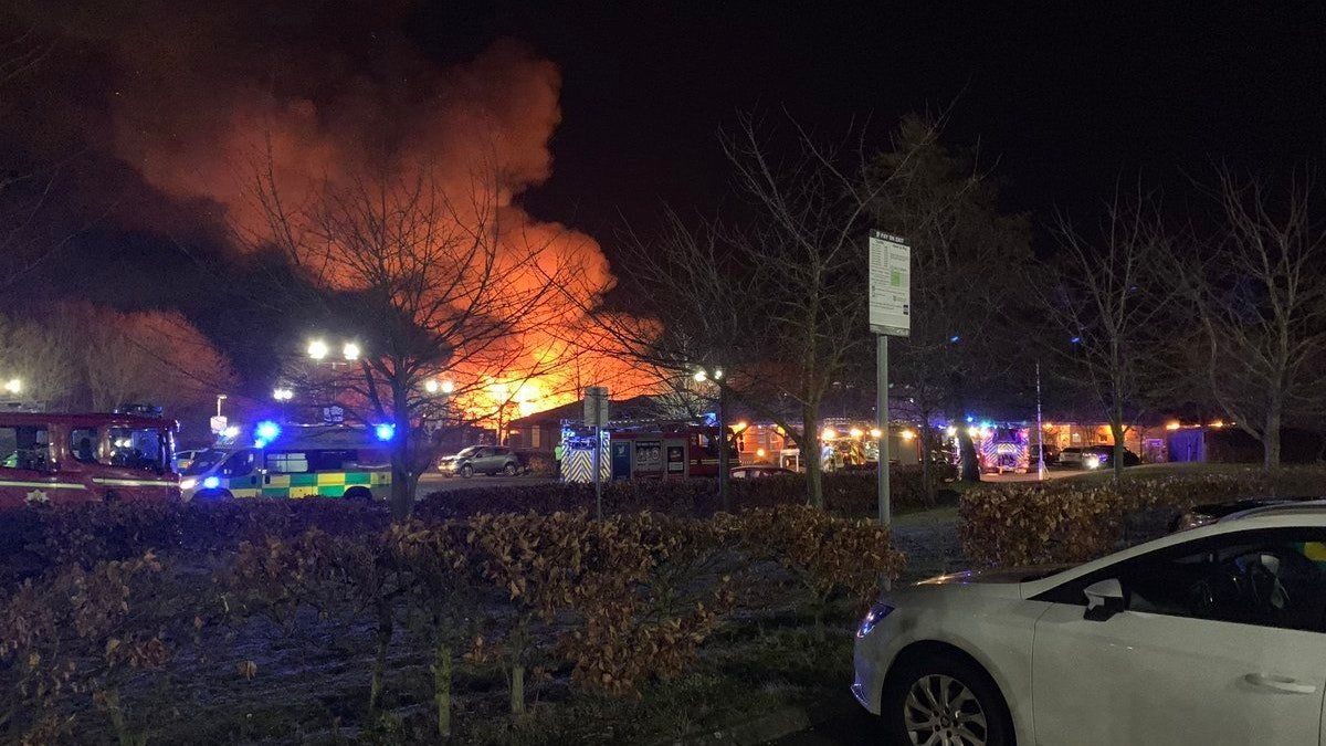 Images showed flames and smoke billowing from the building's roof, part of which appeared to have...