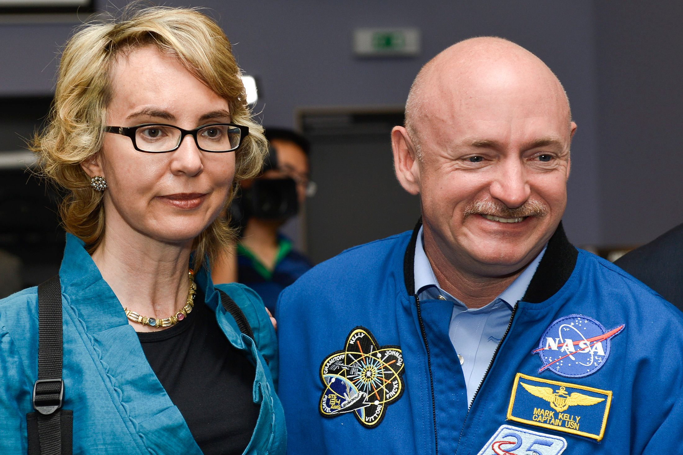 Former U.S. Congresswoman Gabrielle Giffords (L) and her husband Mark Kelly, NASA astronaut and commander of mission STS-134, pose for a picture at the Alpha Magnetic Spectrometer (AMS) Payload Operations and Command Center (POCC) at the European Organization for Nuclear Research (CERN) in Meyrin near Geneva July 25, 2012. The astronauts' visit to the CERN marks the 14th month anniversary of the installation of the cosmic ray detector on the International Space Station (ISS) by the astronauts during the last mission of the space shuttle Endeavour, code-named STS-134, when they flew the Alpha Magnetic Spectrometer for the European Organization for Nuclear Research to the ISS. REUTERS/Valentin Flauraud (SWITZERLAND - Tags: SCIENCE TECHNOLOGY)