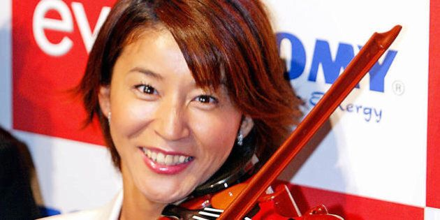 Japanese famous violinist Chisako Takashima tries to play a virtual toy violin 'Evio', produced by Japanese...