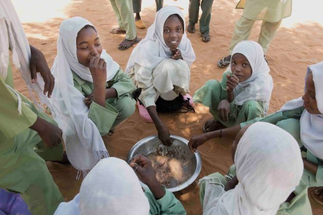 輪になって給食を食べる子供たち(北コルドファン州アルデーバ学校)