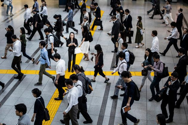 Japanese woman talking on the mobile phone surrounded by commuters walking to