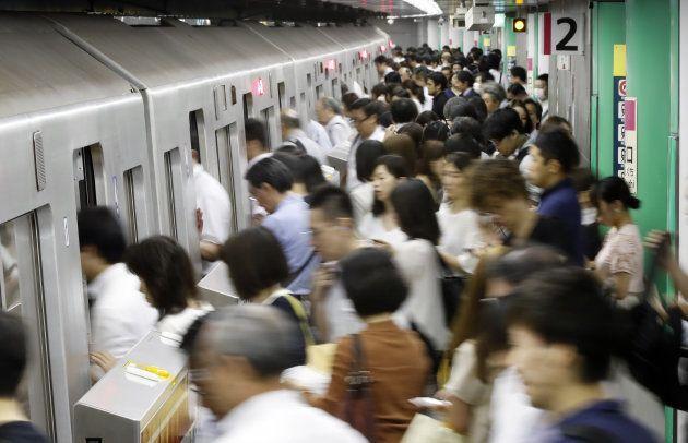 朝の通勤ラッシュで混む都営大江戸線の新宿西口駅のホーム。撮影日:2017年07月11日