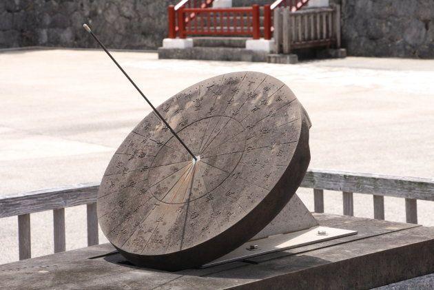日影台。十二支が刻まれた時刻版に銅製の棒が取り付けられ、その日影によって時刻をはかっていたと推測されている。「沖縄戦」で破壊されたが、2000年にかつての形態に復元された。
