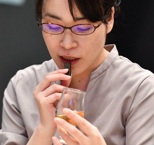 チョコレートを食べながらウイスキーを味わうイベント参加者=5月21日、東京
