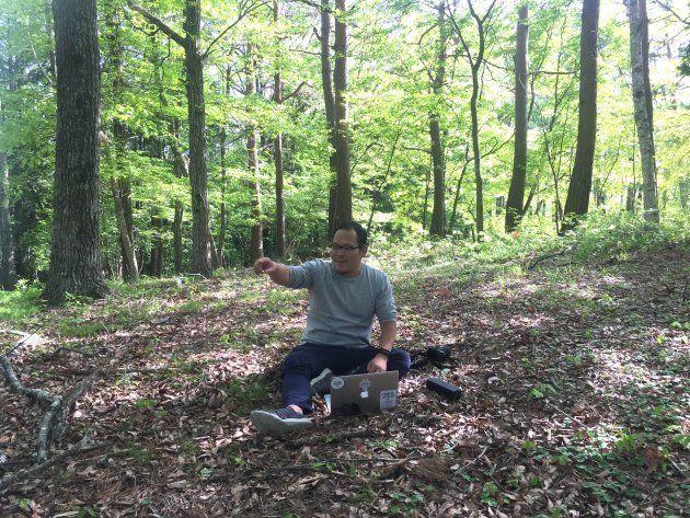 森のオフィスではなく森の中で働く山本さん