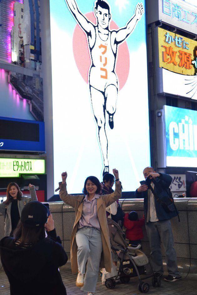 グリコの看板の前でポーズを決めて写真を撮る観光客ら=4月、大阪市中央区道頓堀