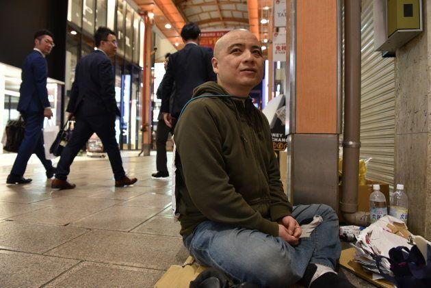 路上に座り、通行人から声がかかるのをじっと待つオドゥー=4月、大阪市中央区