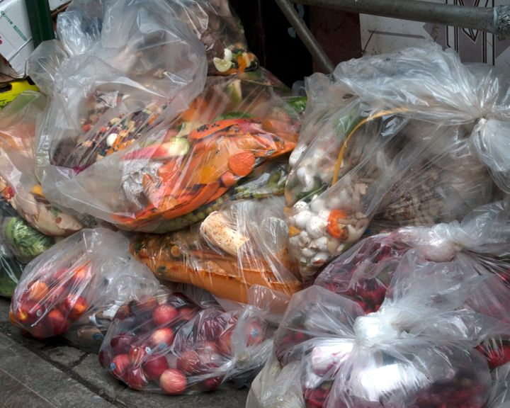 Unsold fresh produce is dumped with the garbage outside a grocery store.