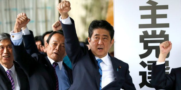 選挙対策本部の看板の前で拳を掲げる安倍首相