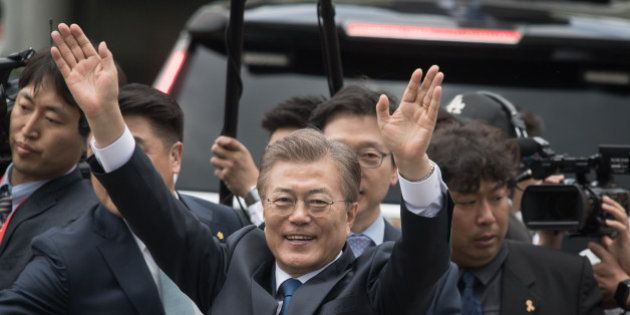 South Korea's President Moon Jae-In waves to his supporters as he greets members of staff as he arrives...
