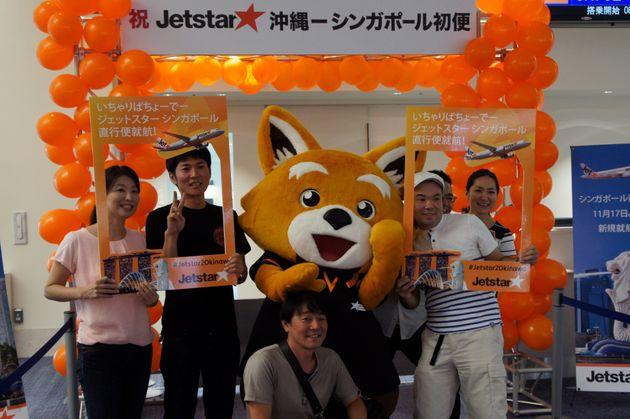 シンガポール線初便の搭乗口で記念撮影する乗客ら=11月17日、沖縄県・那覇空港