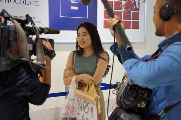報道陣の取材を受けるジェットスター・アジア航空シンガポール線初便の乗客=11月17日、沖縄県・那覇空港