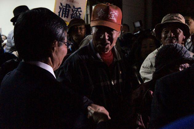 総決起集会後、稲嶺氏(左)と握手して帰る市民(中央)=1月23日、名護市の21世紀の森屋内運動場