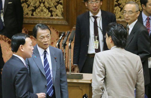 参議院予算委員会が始まらず、退室するため席を立つ麻生太郎副総理兼財務相(左から2人目)。右奥は財務省の太田充理財局長=6日、国会内