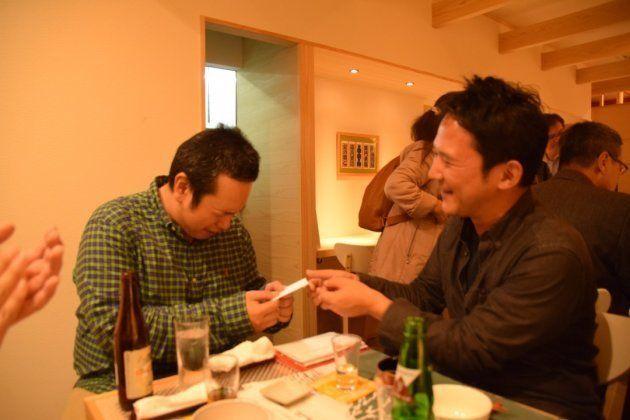落語が終わった後、着替えてお客さんとビールを飲み交わす春風亭一蔵(左)とご祝儀を渡す常連客(右)