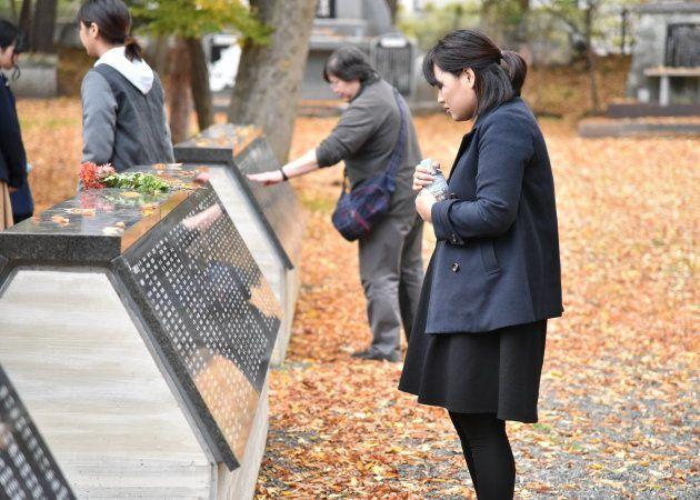 慰霊碑の中から吉岡さんらの名前を探す学生たち