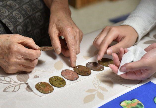 北山さんに手紙を手渡した学生たちは、沖縄で遺骨収集にも取り組んでいる。そこで見つかった兵士らの認識票を北山さんにも見せた=札幌市中央区