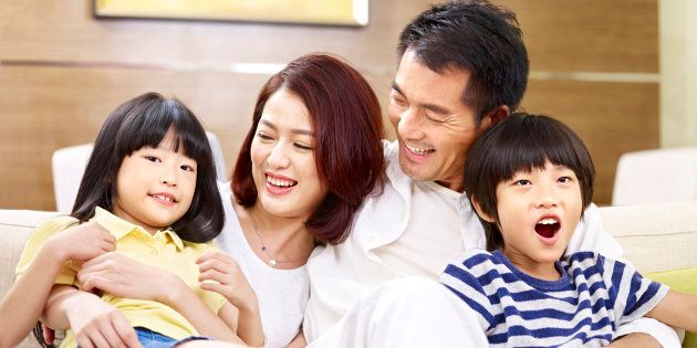 portrait of a happy asian family sitting on couch at home, smiling and