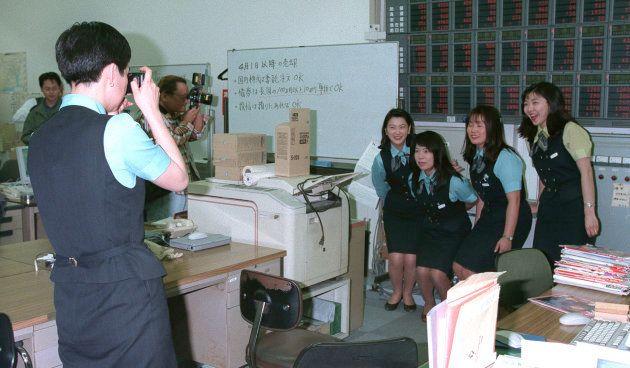最後の業務を終えて、同僚と記念撮影する山一証券の女性社員(東京・新宿)